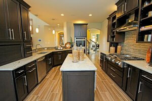 A dark cabinet kitchen with granite countertops